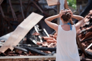 Woman damaged house and holding her head with both hands
